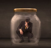 Businessman shut into a glass jar concept. On background Stock Photography