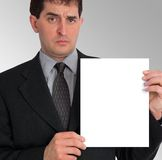 Businessman Side Presentation (Blank). Image of a businessman holding a blank sheet of paper to his left, against a grey gradient background. Taken with a stock images