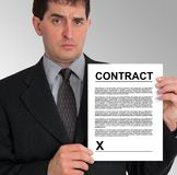 Businessman Side Presentation (Contract). Image of a businessman holding a contract to his left, against a grey gradient background. Taken with a Panasonic FZ30 royalty free stock photos