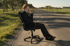 Businessman on the side road in chair Stock Images