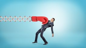 A businessman in side view gets hit with a large red boxing glove attached to a metal scissor arm on a blue background. Business and risk. Strong hit from life Stock Images