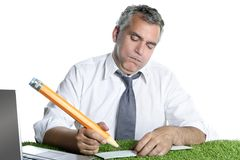 Businessman sign bank check humor gesture. Businessman senior sign bank check funny humor gesture big pencil on green grass stock image