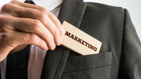Businessman with a sign saying - Marketing. Businessman removing a small rectangular wooden sign saying - Marketing - from the pocket of his suit jacket in a royalty free stock photography