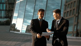 Businessman signature outdoor. Slow motion: Young successful businessmen in suits write signature at his employee document paper. Smile. Glossy business centre stock footage