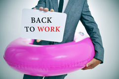 Businessman with a signboard with the text back to work. Businessman with a pink swim ring shows a signboard with the text back to work written in it royalty free stock photography