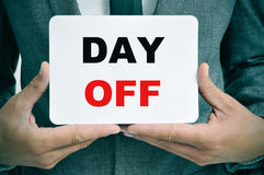 Businessman with a signboard with the text day off Royalty Free Stock Photos