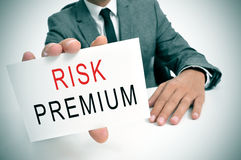 Businessman with a signboard with the text risk premium. A businessman in his office showing a signboard with the text risk premium written in it stock photography