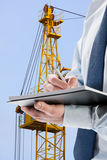 Businessman signing acceptance report / contract. Construction crane in the background Royalty Free Stock Images