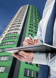 Businessman signing acceptance report / contract. Modern highrise in the background Stock Images