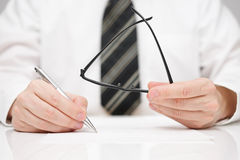 Businessman is signing agreement with glasses in hand Royalty Free Stock Photo