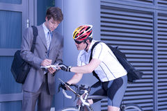 Businessman signing for bicycle courier Stock Image