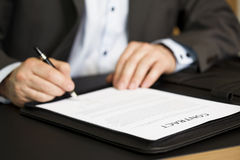 Businessman signing a contract. Businessman in dark suit and blue shirt sitting in office at desk and signing a contract with shallow focus on word contract Stock Photography