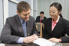 Businessman Signing Contract With Asian Businesswoman Stock Photo