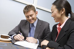 Businessman Signing Contract With Businesswoman Stock Image
