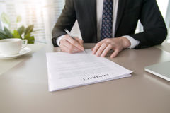 Businessman signing contract. Close up of male hand putting signature in contract, businessman signing document. Successful negotiation concept, agreeing to royalty free stock photo