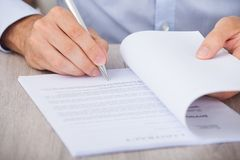 Businessman signing contract at desk Stock Photo