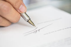 Businessman is Signing a Contract, focus on pen Stock Photo
