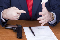 Businessman signing a contract with gun Royalty Free Stock Image