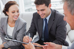 Businessman signing contract while his partner is looking at him. In cosy meeting room Stock Photography