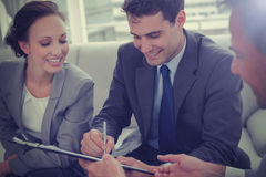 Businessman signing contract while his partner is looking at him Stock Images