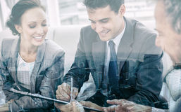 Businessman signing contract while his partner is looking at him Royalty Free Stock Images