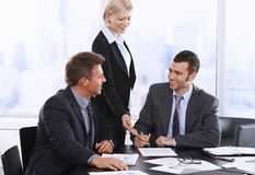 Businessman signing contract. At meeting, smiling assistant pointing at document Stock Image