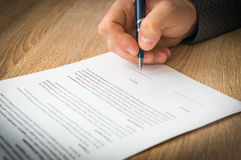 Businessman is signing a contract to conclude a deal Stock Photos
