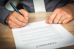 Businessman is signing a contract to conclude a deal Stock Image