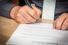 Businessman is signing a contract to conclude a deal Stock Photography