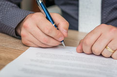 Businessman signing a contract to conclude a deal. Business concept stock image