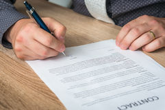 Businessman signing a contract to conclude a deal. Business concept stock photography