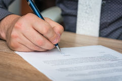 Businessman is signing a contract to conclude a deal. Business concept royalty free stock photos