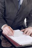 Businessman signing a document. And working at his desk Royalty Free Stock Images