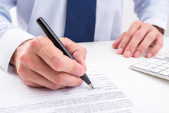 Businessman signing a document. Stock Photo