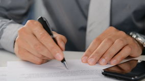 Businessman Signing Document. Close Up Of A Businessman Signing Contract. The male hand signing a business deal in a office. Close up of a signature for a stock video footage