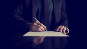 Businessman signing document or contract. Retro image of businessman signing document or contract with silver pen on a black desk with reflection stock photo