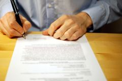 Businessman signing document at desk royalty free stock image