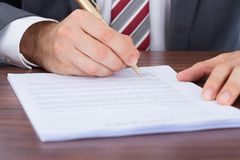 Businessman signing document at desk Royalty Free Stock Photo