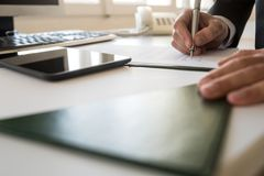 Businessman signing document at his office table in a low angle Royalty Free Stock Images