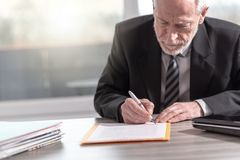 Businessman signing a document (Lorem ipsum text used). Businessman signing a document in office (Lorem ipsum text used royalty free stock photography