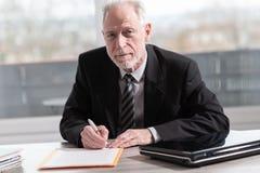 Businessman signing a document (Lorem ipsum text used). Businessman signing a document in office (Lorem ipsum text used stock photography