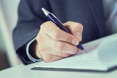Hand of businessman in suit filling and signing with blue pen partnership agreement form clipped to pad closeup. Businessman signing document at table in white stock photography