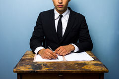 Businessman signing documents at old wooden desk Stock Images