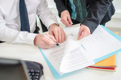 Businessman signing a documents presented by his secretary stock images