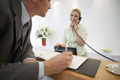 Businessman signing guestbook in reception area, female receptionist using telephone, smiling стоковые фотографии rf