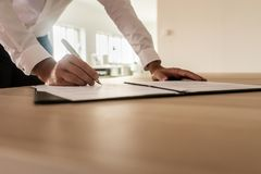 Businessman signing insurance or legal document. Businessman standing at his desk leaning to sign a legal or insurance document in an open folder royalty free stock photo