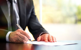 Businessman Is Signing A Legal Document Stock Photo