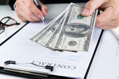 Businessman signing marketing contract.money. Royalty Free Stock Image