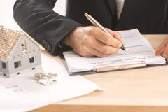 Businessman signing a mortgage  contract. Of a sale for a new house Stock Image