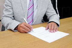 Businessman signing a paper form Stock Image